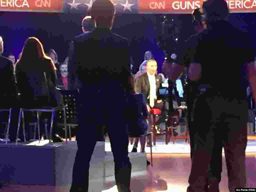 President Barack Obama can be seen through attendees of a CNN televised town hall meeting hosted by Anderson Cooper, not shown, at George Mason University in Fairfax, Va., Jan. 7, 2016.