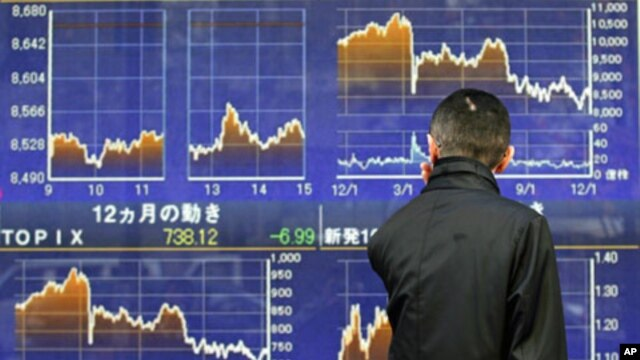 A man looks at a stock quotation board outside a brokerage in Tokyo, December 12, 2011.