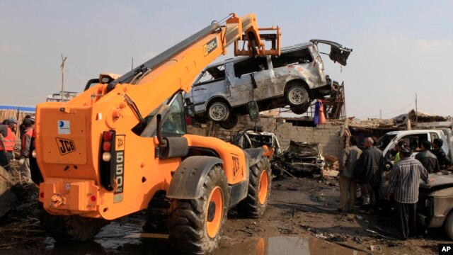 People inspect the scene of a car bomb attack in Baghdad's northern Kazimyah neighborhood, February 8, 2013.