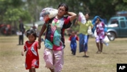 Thai women and children walk to a waiting bus to transport them home after sporadic fighting between Thai and Cambodian troops was reported at a refugee camp in Surin province, northeastern Thailand, May 2, 2011