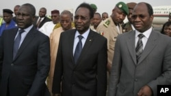Dioncounda Traore, center, Mali's parliamentary head who was forced into exile after last month's coup, walks with Burkina Faso's Foreign Affairs Minister Djibrill Bassole, right, as Traore arrives in Bamako to take up his constitutionally-mandated post a