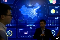 In this April 26, 2018, photo, visitors stand in front of an electronic data display showing a map of China at the Global Mobile Internet conference in Beijing. A California-based security-research firm said Wednesday, July 11, 2018, that it found evidence that an elite Chinese government-linked hacking team has penetrated computer systems belonging to Cambodia's election commission, opposition leaders and media in the months leading up to Cambodia's July 29 election. (AP Photo/Mark Schiefelbein)