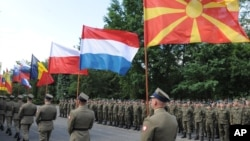 Polish Army soldiers carry flags of some of the countries participating in the Anaconda-16 military exercise, during the opening ceremony, in Warsaw, Poland, Monday, June 6, 2016.