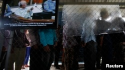 File - People line up to enter the Extraordinary Chambers in the Courts of Cambodia as a television screen shows former Khmer Rouge president Khieu Samphan, in Phnom Penh.