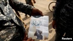 """Seorang tentara Irak menunjukkan pamflet bertuliskan """"Berjanggut itu wajib, dilarang mencukurnya"""" di kota al-Shura, sebelah selatan Mosul (30/10). (Reuters/Zohra Bensemra)"""