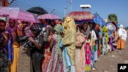 Women who fled the conflict in Ethiopia's Tigray region wait for UNHCR to distribute blankets at Hamdayet Transition Center, eastern Sudan, Nov. 21, 2020.