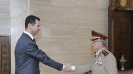 Syria's President Bashar al-Assad (L) welcomes new Chief of General Staff of the Army and the Armed Forces, General Ali Abdullah Ayyoub, before a meeting in Damascus, July 22, 2012.