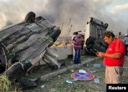 Orang-orang berdiri di dekat mobil yang rusak pasca ledakan di Beirut, Lebanon 4 Agustus 2020. (REUTERS / Issam Abdallah)