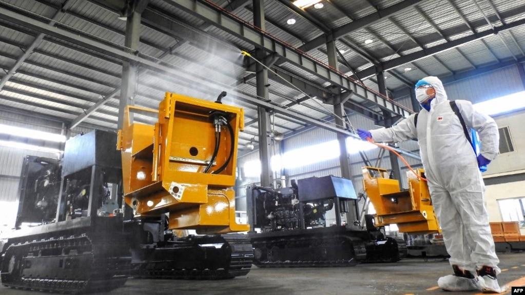 中国江苏省连云港市的一名工人在给工厂的机器喷洒消毒药水为工人节后返工做准备。(2020年2月9日)