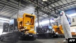 中國江蘇省連雲港市的一名工人在給工廠的機器噴灑消毒藥水為工人節後返工做準備。(2020年2月9日)