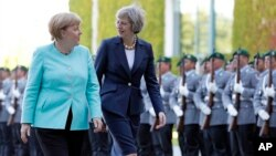 German Chancellor Angela Merkel, left, and British Prime Minister Theresa May walk on the red carpet during a military welcoming ceremony at the chancellery in Berlin Wednesday, July 20, 2016. (AP Photo/Michael Sohn)