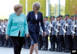 German Chancellor Angela Merkel, left, and British Prime Minister Theresa May walk on the red carpet during a military welcoming ceremony at the chancellery in Berlin, July 20, 2016.