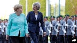 German Chancellor Angela Merkel, left, and British Prime Minister Theresa May walk on the red carpet during a military welcoming ceremony at the chancellery in Berlin Wednesday, July 20, 2016, on May's first foreign trip after being named British prime minister.