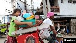 Warga membawa barang-barang mereka, menaiki becak ke pusat penampungan di Tacloban Filipina (4/12/2014) untuk menyelamatkan diri dari topan Hagupit yang diperkirakan akan mencapai Filipina Sabtu.