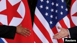 U.S. President Donald Trump and North Korea's leader Kim Jong Un meet at the start of their summit at the Capella Hotel on the resort island of Sentosa, Singapore, June 12, 2018.