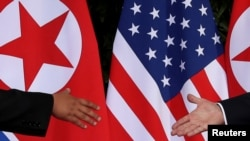 FILE - U.S. President Donald Trump and North Korea's leader Kim Jong Un meet at the start of their summit at the Capella Hotel on the resort island of Sentosa, Singapore, June 12, 2018.