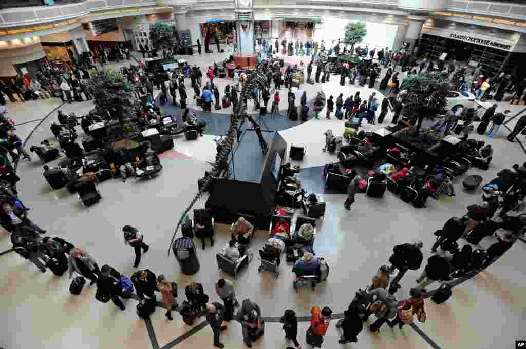 A long line of travelers winds around the atrium at Hartsfield-Jackson International Airport when operations return after the effects of a major winter storm halted flights for three days in Atlanta, Georgia, USA.