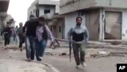 Hình chụp từ video nghiệp dư cho thấy một binh sĩ của phe nổi dậy giúp đỡ một người đàn ông bị thương ở Rastan, Homs, Syria, ngày 15/5/2012