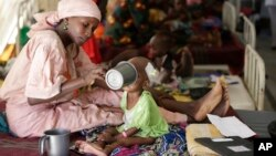 In this 2016 photo, a mother feeds her malnourished child at a feeding center run by Doctors Without Borders in Maiduguri, Nigeria. Officials blame famine-like conditions on Boko Haram militants. ( AP Photo/Sunday Alamba)