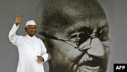 Nhà tranh đấu chống tham nhũng Anna Hazare vẫy tay bên cạnh bức chân dung của ông Mahatma Gandhi trong cuộc tuyệt thực ở New Delhi, Ấn Ðộ, ngày 20 tháng 8, 2011