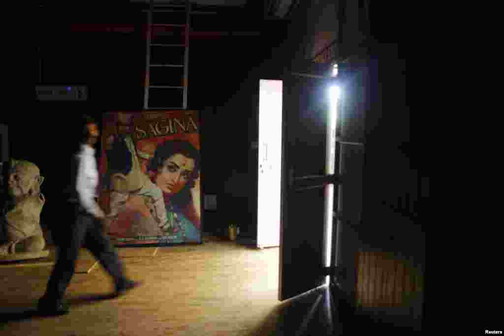 A security guard walks past a Hindi movie poster at an auditorium during a festival celebrating 100 years of Indian cinema in New Delhi, April 30, 2013.