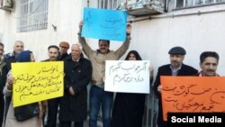 In this image sent to and verified by VOA Persian, Iranian teachers protest in the northeastern city of Mashhad, Feb, 14, 2019. The yellow sign calls for teachers to be paid at equal rates to other public-sector workers, while the blue sign says a teacher's place isn't in prison.