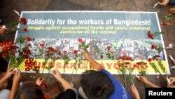 Công nhân ở Manila mang hoa đến và đốt nến trong buổi tập họp, bày tỏ sự đoàn kết với các nạn nhân trong vụ sập xưởng may ở Bangladesh