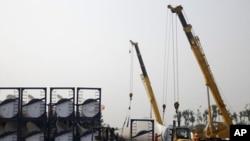 中国天津港工人在装运风力涡轮机浆叶(资料图片)