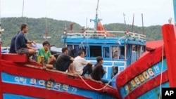 Bức hình chụp ngày 10 tháng 6 năm 2015 được Chính phủ Palau công bố cho thấy ngư dân Việt Nam ngồi trên tàu cá của mình neo đậu ở thành phố Koror, Palau sau khi bị bắt giữ vì đánh bắt hải sâm trái phép trong vùng biển của đảo quốc nhỏ bé này.