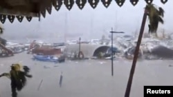 Half-submerged vehicles, boats and debris are seen in the flooded harbor as Hurricane Irma hits the French island territory of Saint Martin, Sept. 6, 2017, in this video grab made from footage taken from social media. (RCI GUADELOUPE/Handout via Reuters)