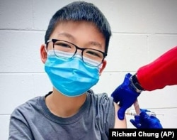 In this Dec. 22, 2020, photo, provided by Richard Chung, his son Caleb Chung receives the first dose of Pfizer coronavirus vaccine or placebo as a trial participant for kids ages 12-15, at Duke University Health System in Durham, N.C. (Richard Chung via AP)