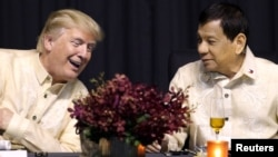 FILE - U.S. President Donald Trump speaks with Philippines President Rodrigo Duterte during the dinner marking ASEAN's 50th anniversary in Manila, Philippines, Nov. 12, 2017.
