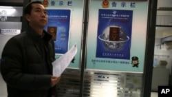 2012年11月23日﹐一名男子行經中國新版護照告示板前