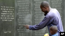 FILE - A survivor pays homage to people killed in the 1998 bombing of the U.S. embassy in Kenya, at the memorial wall in Nairobi, May 2, 2011.