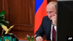FILE - Russian President Vladimir Putin speaks on the phone at the Kremlin, in Moscow, Russia.