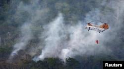 5일 일본 오키나와의 미군 헬리콥터 추락사고 현장에서, 미군 소속의 또 다른 헬리콥터가 사고로 발생한 화재를 진압하고 있다.