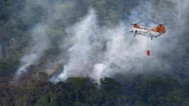 A U.S. military helicopter fights the fire following a crash by another U.S. military CH-46 helicopter, inside Camp Hansen in central Okinawa, on Japan's southern island, in this photo taken by Kyodo, Japan, Aug. 5, 2013.