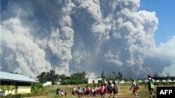 Anak-anak sekolah dasar berjalan bersama di SD Sipandak, Desa Tiga Pancur, di Karo, Sumatra Utara, sementara awan abu tebal menyembur dari Gunung Sinabung, 19 Februari 2018.