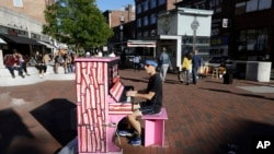 """Street Pianos: In this Sunday, Sept. 25, 2016 photo Scott Frazer, of Medford, Mass., plays a piano on the sidewalk in the Harvard Square neighborhood of Cambridge, Mass. A number of working pianos painted by local artists have been placed around Boston and Cambridge, each with a simple message to passersby: """"Play Me, I'm Yours."""""""