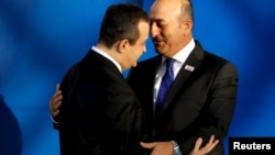 OSCE Chairman Serbian Foreign Minister Ivica Dacic (L) greets Turkish Foreign Minister Mevlut Cavusoglu (R) as he arrives for the OSCE Ministerial Council meeting in Belgrade, Serbia, Dec. 3, 2015.