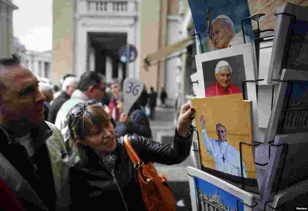 Tourists view newly-printed pictures of the newly-elected Pope Francis, Cardinal Jorge Mario Bergoglio of Argentina, at a souvenir shop near the Vatican in Rome.
