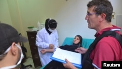 A UN chemical weapons expert meets a person affected by an apparent gas attack, at a hospital where she is being treated in Damascus' suburb of Zamalka, August 28, 2013.