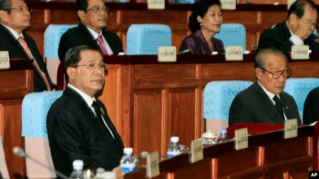 Cambodian Prime Minister Hun Sen, left, sits inside the session hall of the National Assembly with lawmakers from his Cambodian People's Party, in Phnom Penh, Cambodia, Sept. 24, 2013.