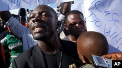 FILE - Vandalark Patricks protests outside Roberts International Airport. Patricks was arrested after he read a communique on behalf of a consortium of political parties and civil society organizations on February 21.