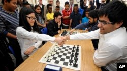 Velemajstori Hou Jifan i Parimardžan Negi rukuju se pred početak partije brzinskog šaha u osnovnoj školi Vogt u Fergusonu u Mizuriju, 13. novembra 2015.