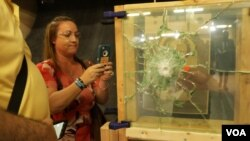 Lori Alhadeff, mother of Alyssa Alhadeff who was killed in the Parkland shooting, inspects safer window options to secure schools. (E. Sarai/VOA)