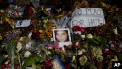 Una foto de Heather Heyer, quien fue asesinada durante una manifestación de nacionalistas blancos, es vista en el suelo, rodeada de flores, en un memorial en celebración de su vida en el teatro Paramount Theater en Charlottesville, Virginia, el miércoles, 16 de agosto de 2017.