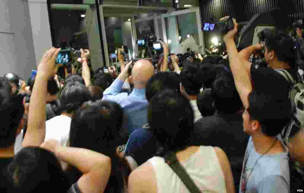 立法會其中一道大門被示威者衝開企圖闖入,警員施放胡椒噴霧,驅散示威者,有人開雨傘遮擋 (美國之音湯惠芸拍攝)
