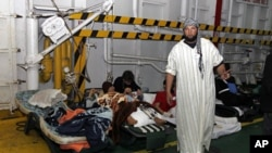 Injured men rest inside a Turkish ship carrying 250 wounded people from the besieged Libyan city of Misrata, at a port in Benghazi, April 3 2011