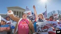 Para aktivis imigrasi berdemonstrasi di depan Mahkamah Agung AS di Washington, DC, mendukung keputusan eksekutif Presiden Brack Obama yang menghapuskan deportasi (18/3). (AP/J. Scott Applewhite)